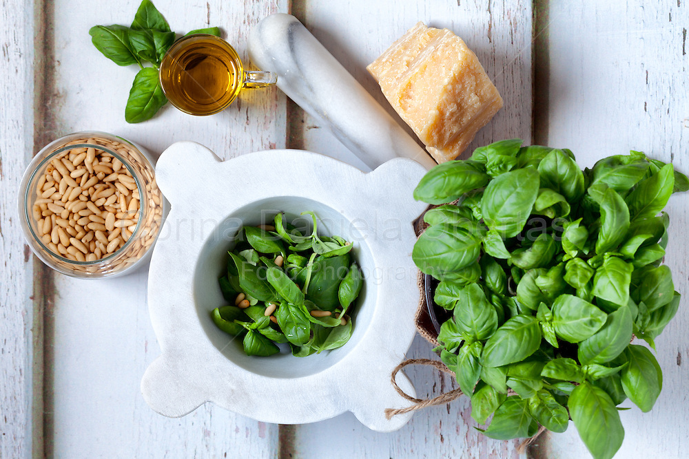 Ingredients for pesto sauce: fresh basil, parmesan cheese, pine seeds and olive oil.