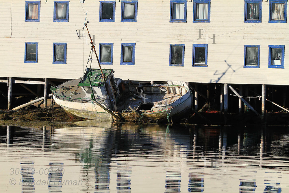 Old fishing boat sits outside fish processing factory in the town of Ingoy on Ingoya island, Finnmark, Norway.