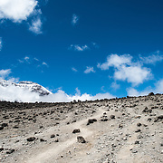 The apline desert on Mt Kilimanjaro Lemosho Route. These shots were taken on the trail between Moir Hut Camp and Lava Tower at approximately 14,500 feet. The mountain's summit is in the distance at left, partly hidden behind clouds.