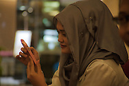 A young Indonesian girl with her iPhone. Many Indonesians own more than one wireless phone.<br /> Various scenes of the city of Jakarta in Indonesia.
