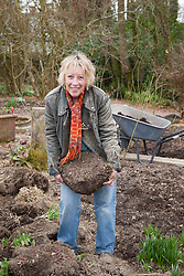 Carol Klein with a clump of Geranium psilostemon that has been dug up from Annie's border and is ready to divide before replanting