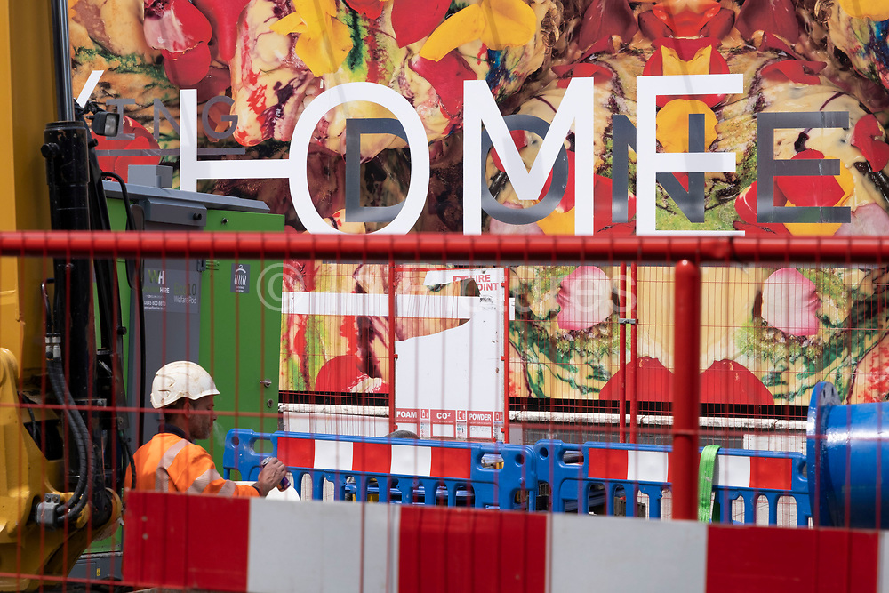 Brightly coloured hoarding surrounding a construction site on The Cut on 1st July 2020 in London, United Kingdom. Graphic colours, stripes and fences cordoned off this area.