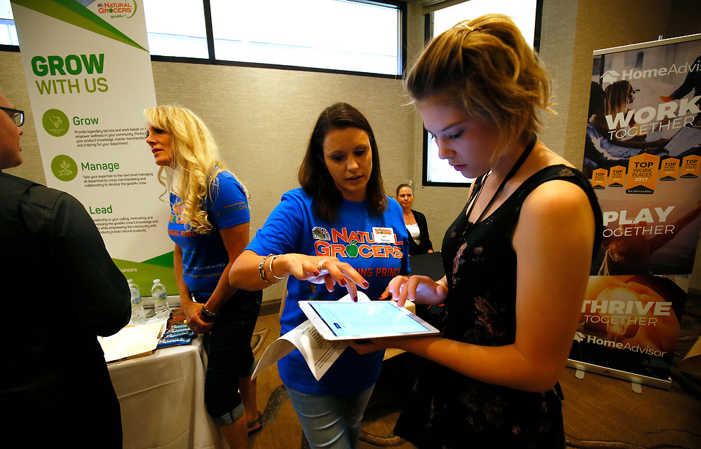 Jen Falkenburg, recruiter for Natural Grocers, shows Cailey Klinger (R) how to fill out an application on a tablet at a job fair in Golden, Colorado June 7, 2016. REUTERS/Rick Wilking