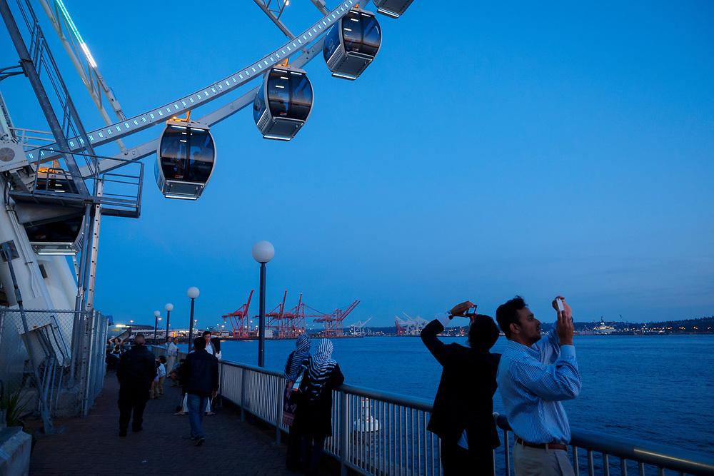 North America, United States, Washington, Seattle. Tourists take photos of the Seattle Great Wheel and Elliott Bay.