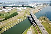 Nederland, Rotterdam, Europoort, 04-07-2006; Dintelhavenbrug, de spoorlijn (Betuweroute) gaat - onder in beeld - richting Maasvlakte, begin van de goederenspoorlijn; rechts van de brug Hartelkanaal, midden en boven: olieopslagtanks en olieraffinaderij, aan de horizon het Calandkanaamet daar achter de Nieuwe Waterweg; economie, infrastructuur, verkeer en vervoer, overslag, haven van Rotterdam, bulkgoederen, economie, scheepvaart; luchtfoto (toeslag); aerial photo (additional fee required); .foto Siebe Swart / photo Siebe Swart