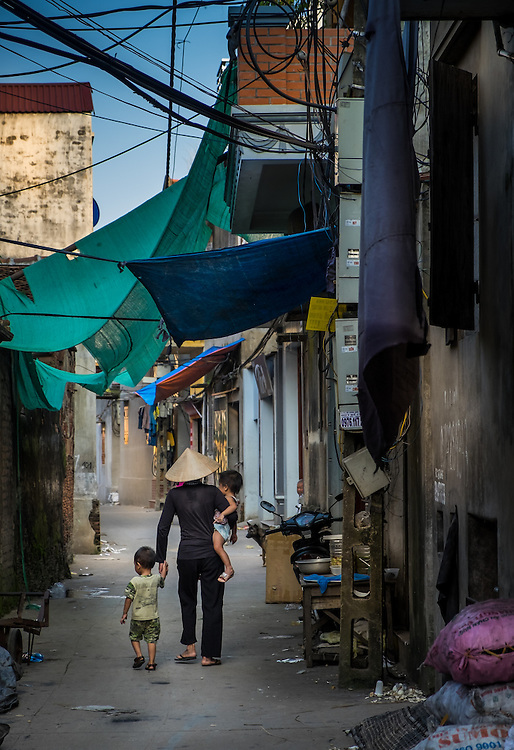 VAN HA, VIETNAM - CIRCA SEPTEMBER 2014: Vietnamese woman with children walking at the Lang Gom Tho Ha village. The village belongs to the Van Ha commune, it is located 50km away from Hanoi in Northern Vietman