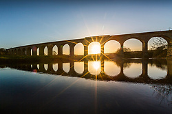 © Licensed to London News Pictures. 28/01/2019. Otley UK. A commuter train crosses Wharfedale viaduct near Otley at sunrise this morning in Yorkshire. Photo credit: Andrew McCaren/LNP