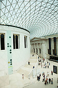 Interior view of the Great Court in The British Museum, London. A Modern highly architectural glass lattice roof covers the entire area.