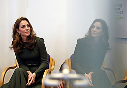 The Duchess of Cambridge watches a video presentation while reflected in a glass door during a visit to Family Action charity's Lewisham base in Forest Hill, Lewisham, London.