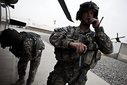 """A flight medic and medical officer don their armor and equipment and check headsets and the start of a mission. Scenes from the medical evacuations of wounded Americans, Canadians, and Afghan civilians and soldiers being flown by Charlie Co. 6th Battalion 101st Aviation Regiment of the 101st Airborne Division. Charlie Co. - which flies under the call-sign """"Shadow Dustoff"""" - flies into rush the wounded to medical care out of bases scattered across Oruzgan, Kandahar, and Helmand Provinces in the Afghan south. These images were taken of missions flown out of Kandahar Airfield in Kandahar Province and Camp Dwyer in Helmand Province."""