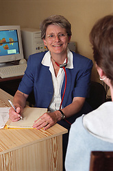 Doctor in community paediatric health centre sitting at desk wearing stethoscope around her neck; listening to patient and smiling,