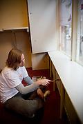 In het kader van de vrijwilligersdag verven twee medewerkers van een verzekeringskantoor de ruimte van daklozenkrant Straatnieuws in Utrecht