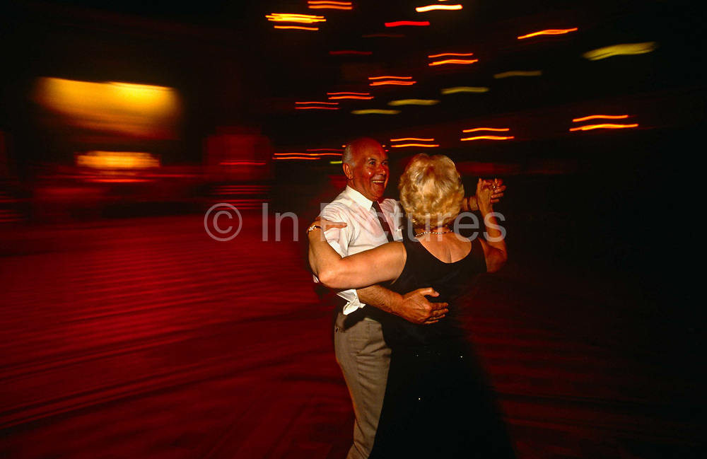 An elderly couple dance on the wide dance floor at Blackpool Tower Ballroom, England. They are the only dancers in the empty dance space, except for the Wurlitzer organist who is playing his accompanying music at the front of the stage, in a pool of bright light. We are looking down from a balcony high above and the husband and wife are pausing during their dance routine, stopping just long enough to register as sharp figures in the picture. The Ballroom is the traditional home of the mighty Wurlitzer Organ and complemented by the 3 Deck Wersi - the world's most advanced organ. The Wersi is a state-of-the-art Louvre organ played by the resident organists in this magnificent setting. The present interior of the Blackpool Tower circus was created by the famous theatre designer, Frank Matcham and completed in 1900.