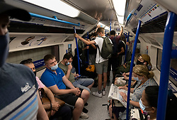 © Licensed to London News Pictures. 19/07/2021. London, UK. Passengers on a Victoria line Underground train en-route to Euston Station on the morning of Freedom Day. All covid regulations in England are being scrapped from today even though infections and hospitalisations are on the increase. Photo credit: Peter Macdiarmid/LNP