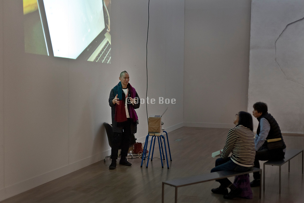 artist Yosuke Amemiya talking during his performance at the Domani / The Art of Tomorrow show in the National Art Center Tokyo.  February 2018