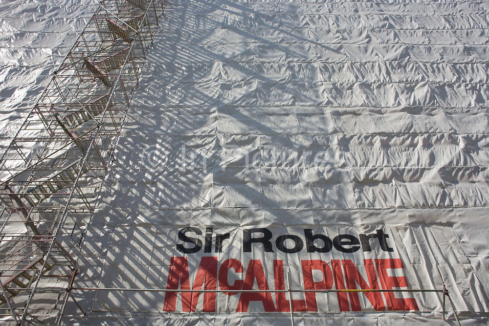 """Protective sheeting surrounds a tall building project undertaken by the by British construction company McAlpine in Victoria Street, London. Sidelit from the left, the shadows from a rising steps and supporting scaffolding, the company brand is written in large black and red letters, printed on the shrouding covers. Sir Robert McAlpine is a leading UK building and civil engineering company. It carries out engineering and construction for the oil and gas, petrochemical, power generation, nuclear, pharmaceutical, defence, chemical, water and mining industries. The company was founded in 1869 by Sir Robert McAlpine, who was known as """"Concrete Bob""""."""