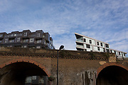 New apartment homes rise above a Victorian railway bridge in Southwark, on 13th November 2017, in London, England.