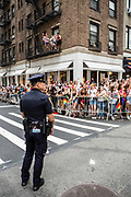 New York, NY - 25 June 2017. New York City Heritage of Pride March filled Fifth Avenue for hours with groups from the LGBT community and it's supporters. A policeman surveys the crowd of spectators, some of whom are on a balcony overlooking W. 22d Street.