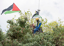 © Licensed to London News Pictures; 20/05/2021; Bristol, UK. Bailiffs use a crane to lift a man off a scaffold tripod blocking the entrance to the site. Police and bailiffs evict occupants squatting on the site of a former gas works belonging to Wales and West on Glenfrome Road. The site is occupied by around 75 people including children mostly living in vehicles and caravans. Police led some occupants away and released them. The site was evicted last year. Photo credit: Simon Chapman/LNP.