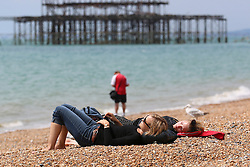 © Licensed to London News Pictures. 20/06/2014. Brighton, UK. Two woman sleeping on the beach in the sunshine in Brighton. Warm weather is expected accross the UK over the weekend. Photo credit : Hugo Michiels/LNP
