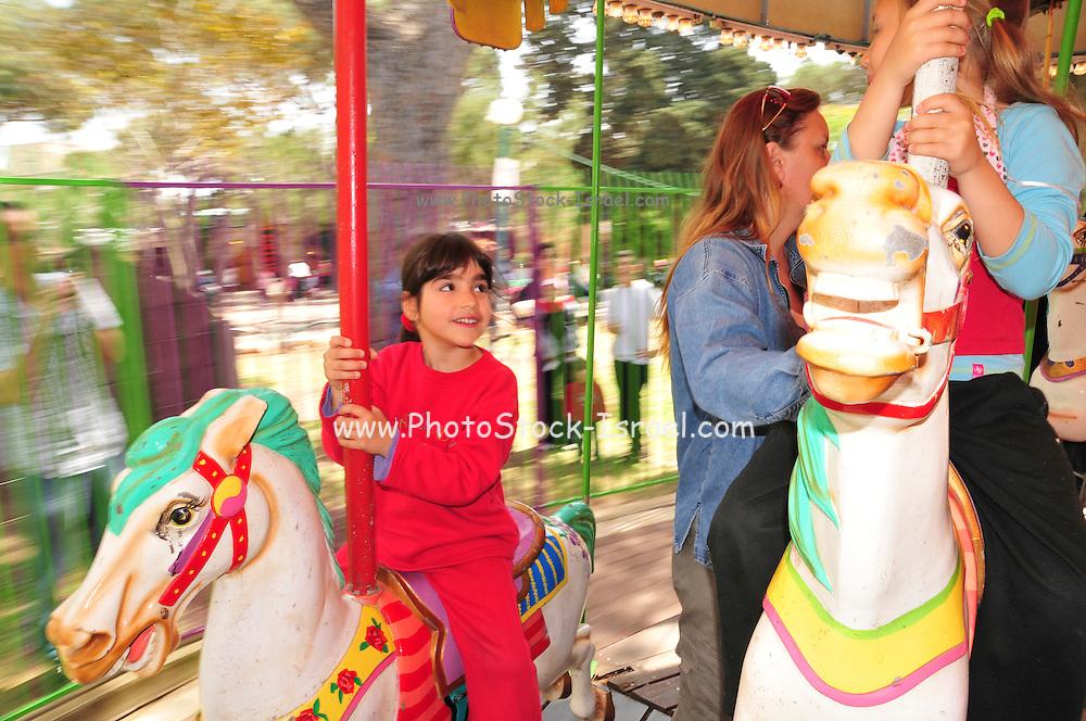 """Israel, Haifa, Gan Ha'em (""""the mother's garden"""") on the Carmel Mountain Children on a merry-go-round"""