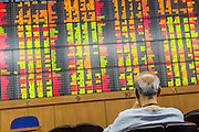 02 SEPTEMBER 2013 - BANGKOK, THAILAND:  A man watches real time changes in the Thai stock market on the stock ticker at Asia Plus Securities headquarters in central Bangkok. The Thai stock market has declined more than 20% from its 2013 high as data as Thailand entered a recession in the second quarter. The loss of value in the Stock Exchange of Thailand (SET) is the greatest sell off since the end of the Asian financial crisis in 1998. Foreign investors have sold more than $1 billion of local shares this month amid signs of slowing regional economic growth and speculation that the U.S. Federal Reserve will soon cut its stimulus.     PHOTO BY JACK KURTZ