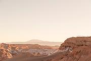 Visitors watching sunset over horizon on desert, Valle de la Luna, Atacama Desert, Chile