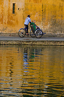 Cyclo riding along the picturesque Hoi an waterfront in beautiful late afternoon light.