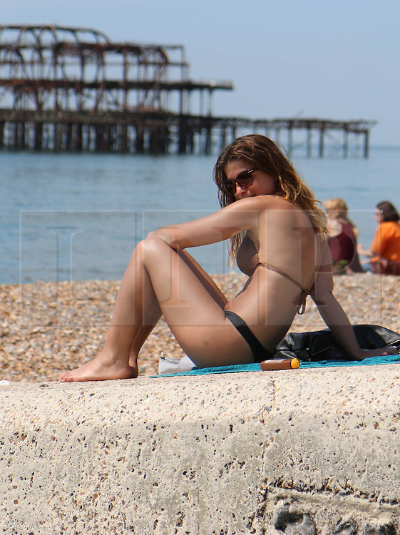 © Licensed to London News Pictures. 13/06/2014. Brighton, UK.A woman sunbathing on Brighton beach. Today, Friday 13th June is expected to be the hottest day of the year so far with temperatures hitting nearly 30C at some locations. Brighton beach is slowly filling up with sunbathers and people wanting to relax by the beach. Photo credit : Hugo Michiels/LNP