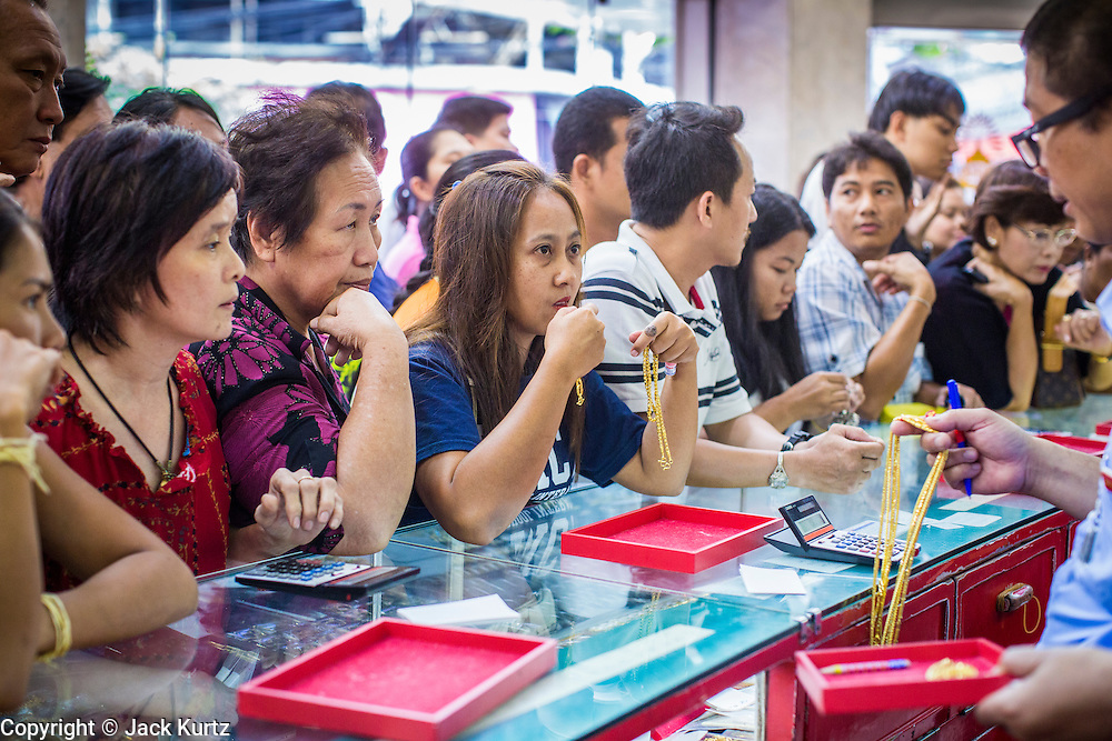 17 APRIL 2013 - BANGKOK, THAILAND:   A woman talks to a salesman about a gold necklace she was buying in a Bangkok gold shop Wednesday morning. Thais flocked to gold shops in Bangkoks's Chinatown this morning to buy gold. Wednesday was the first day most gold shops were open after a five day holiday weekend. Shops were closed Friday through Tuesday, when global gold prices dropped by more than 13% based on jitters that Cyprus might liquidate its gold stocks. The Thailand Futures Exchange (TFEX) suspended trading of all gold and silver futures for a short time Tuesday morning because of instability in the market. Gold is now about 22 percent below the record peak of $1,920.30 an ounce set in September 2011. Thais buy gold as both jewelry and an investment, a hedge against inflation and financial failures. Bangkok's Chinatown district is the center of Thailand's gold trade.  PHOTO BY JACK KURTZ