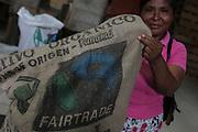 Semiramis Bonilla, Ngäbe woman and member of COCABO, holds a cocoa beans sack with the Fair Trade logo on it. COCABO: Almirante, Changuinola, Bocas del Toro, Panamá. September 1, 2012.