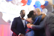 Garden City, New York, USA. November 6, 2018. NYS Assemblywoman-elect TAYLOR RAYNOR, District 18, hugs man on stage, as Nassau County Democrats watch Election Day results at Garden City Hotel, Long Island.  Some other Democratic elected officials in Nassau County joined them on stage.