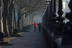 London, February 24th 2016. Two runners jog along Cheyne Walk beside the River Thames as the sun rises on a chilly but clear morning in London. ©Paul Davey<br /> FOR LICENCING CONTACT: Paul Davey +44 (0) 7966 016 296 paul@pauldaveycreative.co.uk