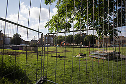 London, UK. 14th August, 2021. Fencing has been installed around Peckham Green by Southwark Council, which plans to develop it as public housing. Peckham Green is a 1.4-acre public park off Peckham High Street, one of the most polluted roads in London, in a borough which is ranked fifth-worst in London and eighth-worst in the UK for easy access to green space, and local residents and campaigners have been protesting that they were not consulted by Southwark Council in relation to its plans.