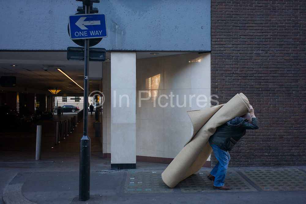A workman manhandles a heavy roll of carpet in a Mayfair street, central London. Struggling under the awkward load, the man is hunched to take the weight as he makes his way towards his van, the process of removing the rug away. Above his head we see the sign pointing in the opposite direction - as if the wrong way according to the whatever rules apply.