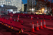Night scene of bollards and a road blocked off under red lighting on Broad Street in Birmingham, United Kingdom.