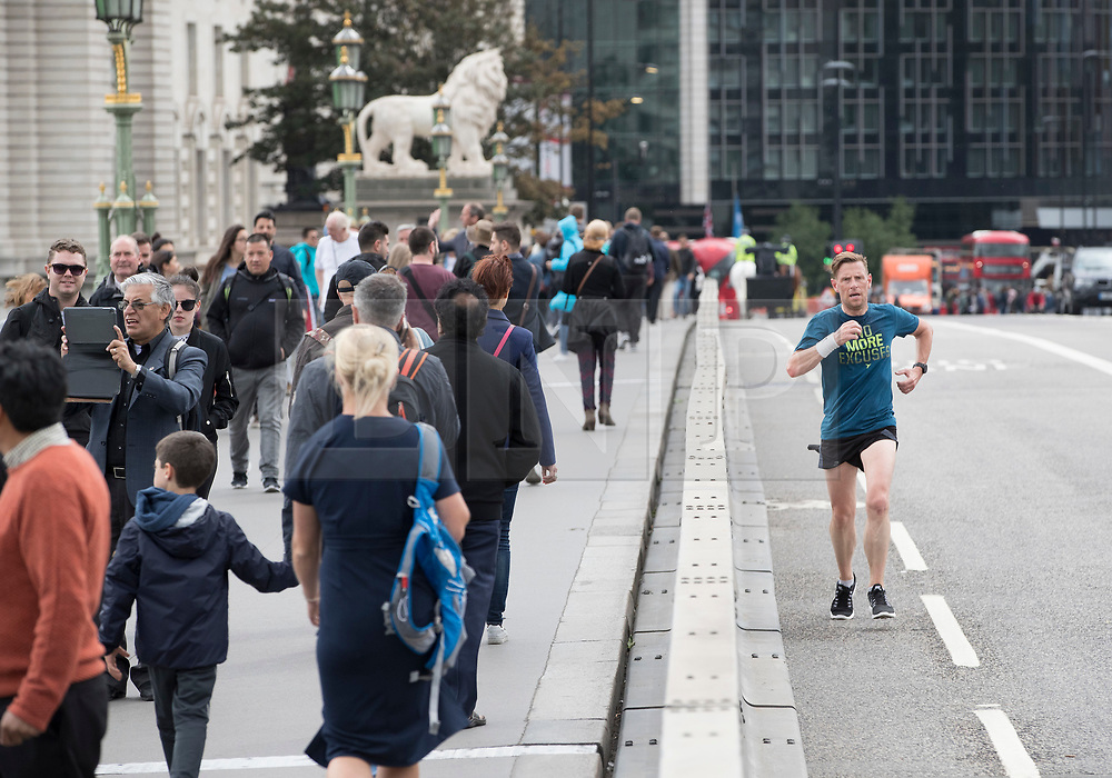 © Licensed to London News Pictures. 05/06/2017. London, UK. A jogger runs past new security crash barriers installed along Westminster Bridge in London following a terrorist attack on London Bridge on Saturday evening, in which a group of three men drove a hired van at pedestrians. New security measure are being implemented across the capital to prevent a repeat of recent attacks. Photo credit: Peter Macdiarmid/LNP