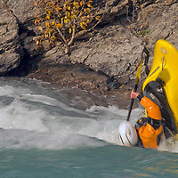 Play boat kayaker Bryce Shaw (MR)  surfs waves on Kananaskis River, Kananskis Provincial Park, near Banff and Calgary, Alberta, Canada