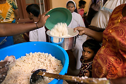 Rice is distributed among members of the small Christian village Dutch Bar, Batticaloa, Sri Lanka, March 7, 2005. Residents of the village spent more than six weeks in a makeshift refugee camp at the local convent recovering from the devastating tsunami that hit the eastern and southern borders of Sri Lanka. They were then moved into another temporary living camp, while awaiting the building of new homes. More than 150 Residents in this community of less than 1000 people died in the tragic event.