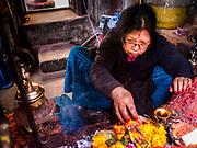 13 MARCH 2017 - PATAN, NEPAL: A woman sets out a small offering in a Hindu temple in Patan's Durbar Square.      PHOTO BY JACK KURTZ    PHOTO BY JACK KURTZ