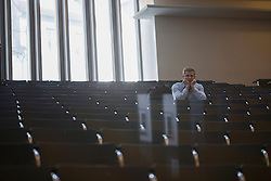 Bored college student sitting alone in lecture hall and listening lecture, Freiburg im Breisgau, Baden-Wuerttemberg, Germany