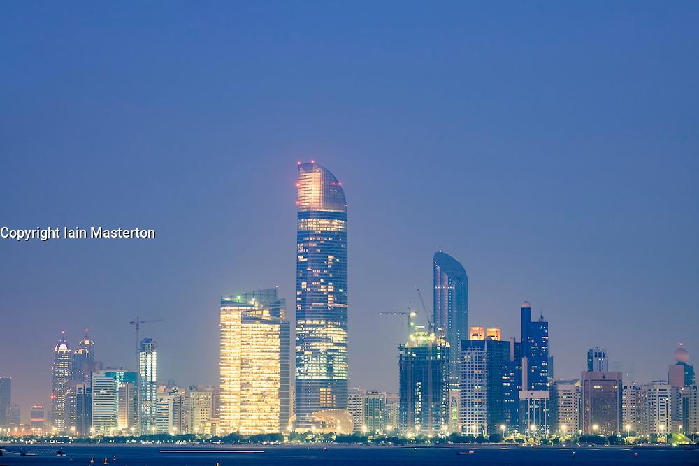 Skyline of modern skyscrapers at night along Corniche in Abu Dhabi United Arab Emirates