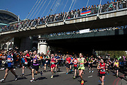 London, UK. Sunday 13th April 2014. Competitors running in the main public event of the Virgin Money London Marathon 2014. These runners take part and raise huge sums fo money for charity organisations. Passing underneath Golden Jubillee Bridge and Hungerford Bridge.