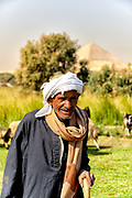 Shepherd in Dahshur lake with Bent pyramid in the distance behind him