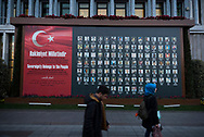 Outside Istanbul's city hall, two pedestrians walk past a memorial showing the pictures of Turkish citizens who died resisiting an attempted military coup on July 15, 2016.