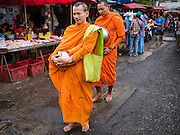 01 DECEMBER 2016 0 BANGKOK, THAILAND: Buddhist monks in the traditional market on Lan Luang Road in Bangkok. The market is on the site of one of the first western style cinemas in Bangkok. The movie theatre closed years ago and is still empty but the market fills the streets around the theatre.     PHOTO BY JACK KURTZ