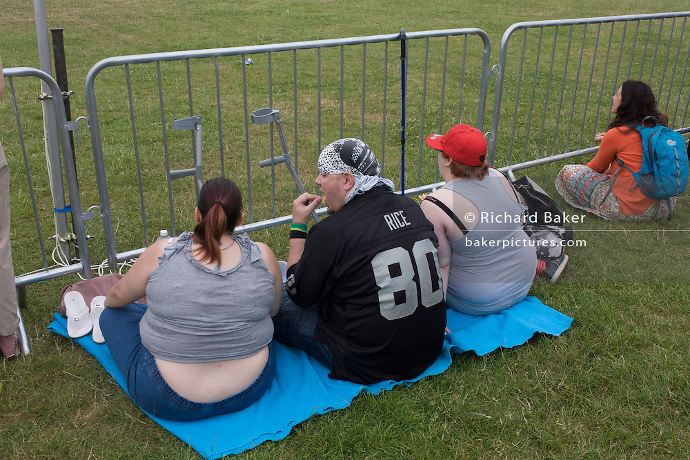 Three large family members eat a picnic in a south London park.