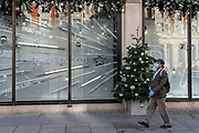 After a bleak year of Coronavirus pandemic misery, a shopper wearing a face mask and gloves walks past the temporary Christmas-themed Harvey Nichols window which urges Londoners to be optimistic for the coming year, on 13th November 2020, in London, England.