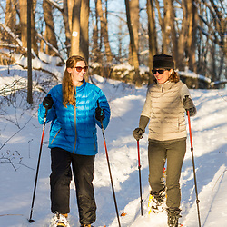 Two women snowshoe in the forest on Indian Hill in West Newbury, Massachusetts.