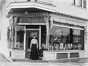 9304-106. store at 1405 NE Sandy, which is now 5115 NE Sandy after renumbering. Reflection in window is  across street from Hubbel & Son, which was at 1421 Sandy, near corner of 52nd.